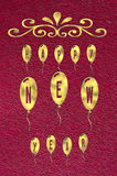 Text Happy New Year written on golden glossy balloons on red leather background Royalty Free Stock Photo