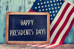 Text happy presidents day in a chalkboard and the flag of the US. The text happy presidents day written in a chalkboard and a flag of the United States, on a Royalty Free Stock Photo