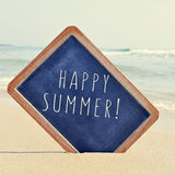 Text happy summer in a chalkboard on the sand of a beach, with a Stock Photos