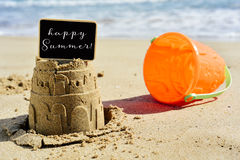 Text happy summer in a signboard topping a sandcastle Stock Image