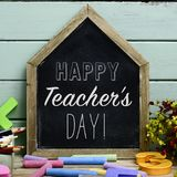 Text happy teachers day in a chalkboard. A house-shaped chalkboard with the text happy teachers day written in it, on a rustic wooden table full of pieces of Royalty Free Stock Photo