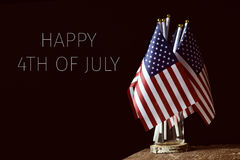 Text happy 4th of july and american flags. Some american flags in a glass jar, on a rustic wooden surface and the text happy 4th of july on a black background stock images