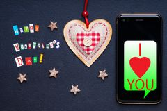 Text Happy Valentine`s day made with carved letters, smartphone, star and heart shape stock image