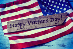 Text happy veterans day and the flag of the US. The text happy veterans day written in a piece of wood and a flag of the United States, on a blue rustic wooden Stock Photography