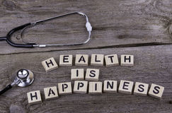 Text: HEALTH IS HAPPINESS from wooden letters on wooden backgrou Stock Photography