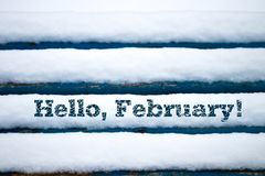 Text Hello February on old wood texture with snow Royalty Free Stock Photo