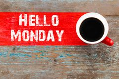 Text HELLO MONDAY and cup of aromatic coffee on wooden background, closeup stock image