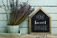 Text home sweet home in a house-shaped signboard. Closeup of a house-shaped chalkboard with the text home sweet home written in it and a bunch of lavender Royalty Free Stock Photo