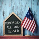 Text honoring all who served and american flag. The text honoring all who served written in a house-shaped chalkboard and a flag of the United States, against a Royalty Free Stock Images
