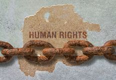 Text Human Rights. Written on rough background and a thick rusty chain royalty free stock photos