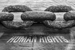 Text Human Rights. Written on rough wooden background and a thick chain royalty free stock photography