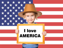 Text I love AMERICA. Little Funny girl in striped shirt with blackboard. Text I love AMERICA. On background of  American flag Royalty Free Stock Image