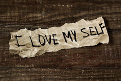 Text I love myself written in a piece of paper. The text I love myself written in a piece of paper, placed on a rustic wooden surface Royalty Free Stock Image