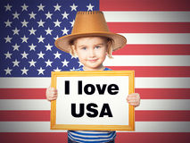 Text I love USA. Little Funny girl in striped shirt with blackboard. Text I love USA.  On background of  American flag Royalty Free Stock Photo
