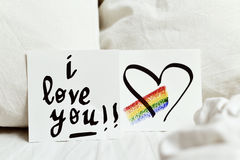 Text I love you in a note. A white paper note with the text I love you and a rainbow and a heart drawn in it, placed on the white sheets of an undone bed Stock Images