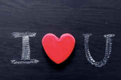 Text I love you, written in chalk on black board. Stock Images
