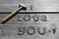 Text I LOVE YOU written by metal nails. On wooden background stock photos