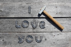 Text I LOVE YOU written by metal nails. On wooden background royalty free stock image