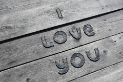 Text I LOVE YOU written by metal nails. On wooden background stock images