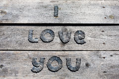 Text I LOVE YOU written by metal nails. On wooden background stock photography