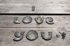 Text I LOVE YOU written by metal nails. On wooden background royalty free stock images