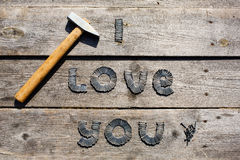 Text I LOVE YOU written by metal nails. On wooden background royalty free stock photography