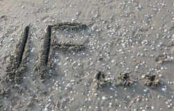 Text IF on the sand of the sea waiting to be erased by the water. Of the sea Royalty Free Stock Photo
