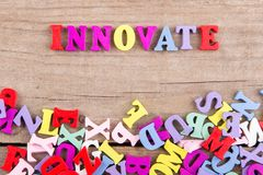 Text `Innovate` of colored wooden letters. On a wooden background royalty free stock photos