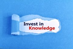 Invest in Knowledge. The text Invest in Knowledge appearing behind ripped blue paper royalty free stock photo