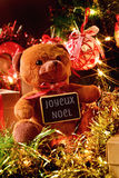 Text joyeux noel, merry christmas in french. Closeup of a teddy bear with a chalkboard with the text joyeux noel, merry christmas written in french, and some Stock Image