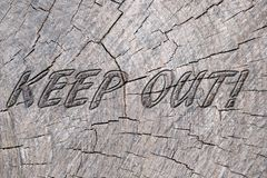 Keep out. Text keep out in wood background stock images