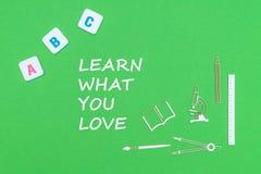 Text lär vad du älskar, från ovannämnd träminituresskolatillförsel och abc märker på grön bakgrund Arkivfoto