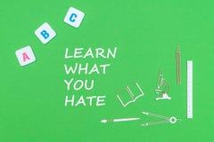 Text lär vad du hatar, från ovannämnd träminituresskolatillförsel och abc märker på grön bakgrund Royaltyfria Foton