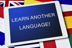 Text learn another language in a tablet computer. The text learn another language in the screen of a tablet computer surrounded by flags of different countries Royalty Free Stock Photos