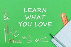 Text learn what you love, school supplies wooden miniatures, notebook with ruler, pen on green backboard. Concept school, text learn what you love, school Stock Photos
