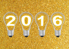 Text 2016 in lightbulb on gold glitter background. S royalty free stock photo