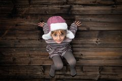 Text or logo empty copy space in vertical top view dark vintage wood.Beautiful happy smiling child girl in homewear. Childhood concept.Xmas winter holiday stock photography