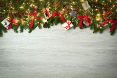 Text or logo empty copy space in vertical top view white wood with pine branches,ribbons and lights decorated frame.Xmas. Winter holiday season party social stock images