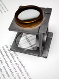 Text and loupe. Macro detail of text and loupe on offset printed sheet Stock Photos