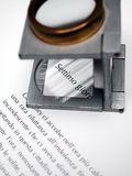 Text and loupe. Macro detail of text and loupe on offset printed sheet Stock Photography