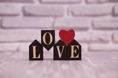 Text love on black wooden blocks with red heart on white brick background. Happy Valentines womans mothers day stock photo
