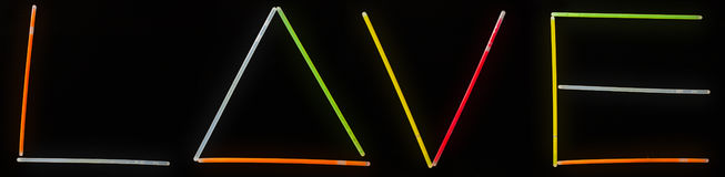 Text love of glow sticks,. Neon sticks on a black background Stock Photo