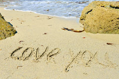 Love you written on sandy beach Stock Images