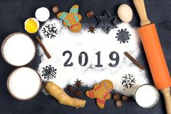 2019 text made with flour with decorations on a black background. 2019 text, snowflakes  made with flour with decorations on a black background. Flat lay. Merry stock image