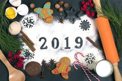 2019 text made with flour with decorations on a black background. 2019 text, snowflakes made with flour with decorations on a black background. Flat lay. Merry stock photo
