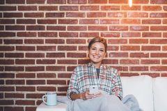 That text made my day. Attractive young blonde woman smiling and using a cellphone while sitting on her sofa wrapped in a blanket Stock Images