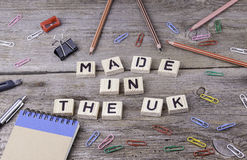 Text: MADE IN THE UK from wooden letters on wooden background.  royalty free stock photography