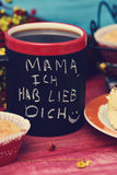 Text mama ich hab lieb dich, I love you mom in german. The sentence mama ich hab lieb dich, I love you mom in german handwritten with chalk in a black mug with Stock Photo