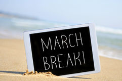 The text march break in a tablet computer on the beach Royalty Free Stock Photos