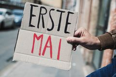 Text may day in german in a cardboard signboard. Closeup of a young caucasian man outdoors showing a brown cardboard signboard with the text erste mai, may day royalty free stock photos